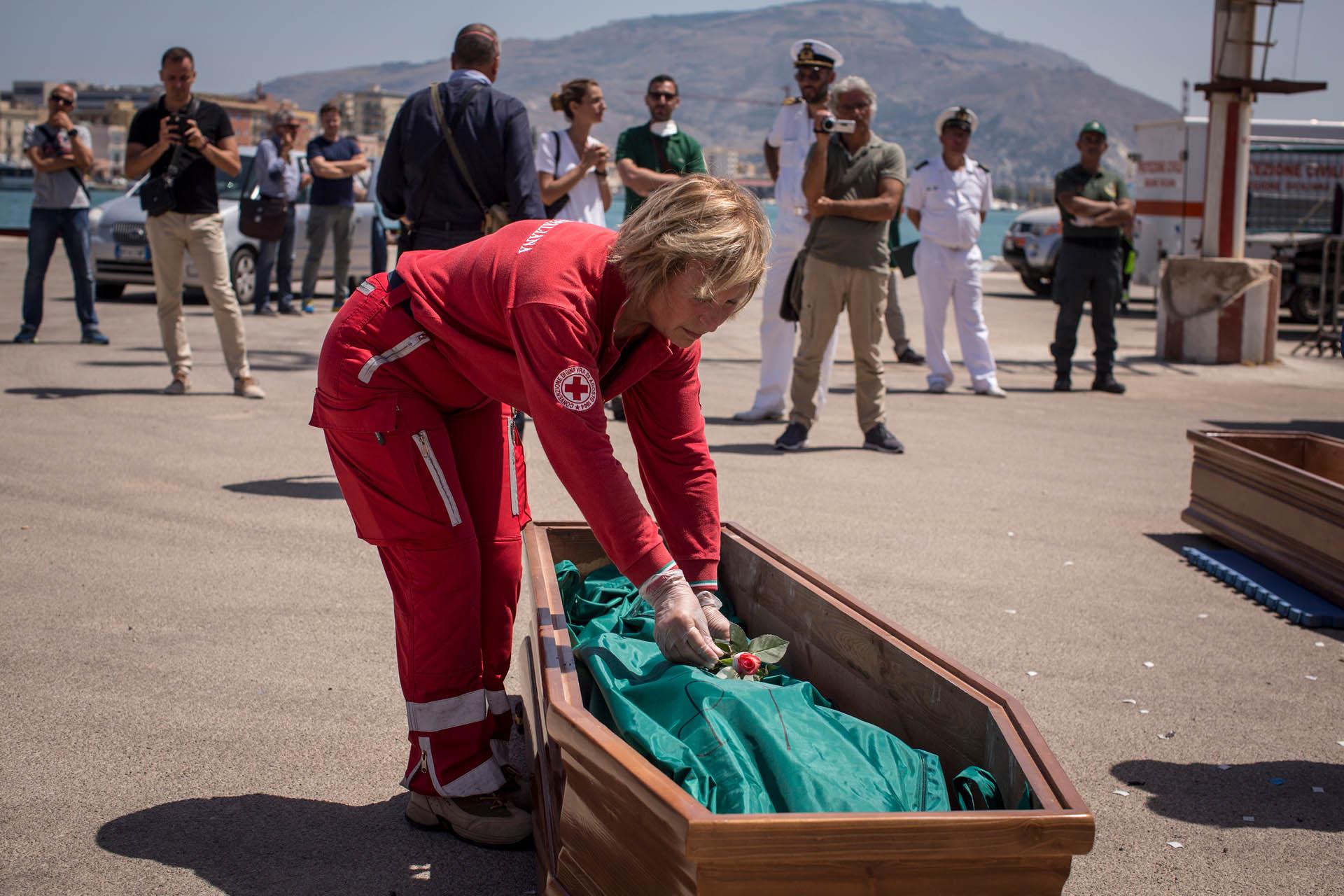 Eine Ärztin legt eine rote Rose in den Sarg eines Flüchtlings, der immer Mittelmeer starb. (Foto: Anna Psaroudakis)